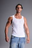 Muscular Young Man. Standing in jeans and a white wife beater tee shirt stock image