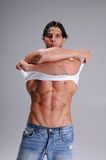 Muscular Young Man. Standing in jeans and taking off a white wife beater tee shirt royalty free stock photo