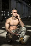 Muscular young man in abandoned warehouse sitting Stock Photo