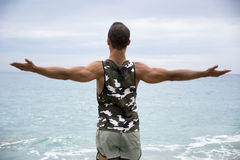 Muscular young man on the beach seen from the back Stock Photo
