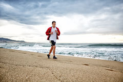 Muscular young man in bright sportswear running on the beach along the sea, HDR effect. Morning jog, fitnes and healthily lifestyle royalty free stock photos