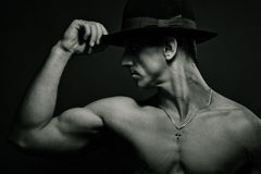 Muscular young man. Bw. Portrait of young muscular man with hat in studio. Black and white Stock Photography