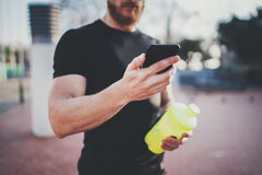 Muscular young man checking burned calories on smartphone application after good workout outdoor session on sunny park Stock Photography