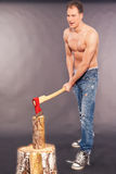 Muscular young man chopping logs Royalty Free Stock Images