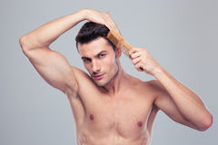 Muscular young man combing his hair Stock Image