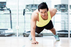 Muscular young man doing one armed pushups in gym Stock Images