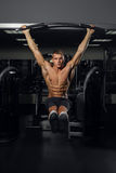 Muscular young man doing pull up on horizontal bar Royalty Free Stock Images