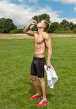 Muscular young man drinking water Royalty Free Stock Image