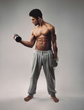 Muscular young man exercising with dumbbells stock images