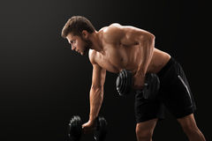 Muscular young man exercising with dumbbells stock photo