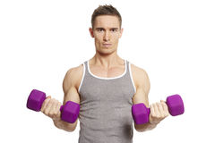 Muscular young man exercising in sports outfit Royalty Free Stock Photography