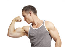 Muscular young man flexing arm muscles in sports outfit. On white background stock photos