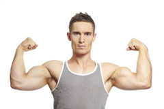 Muscular young man flexing arm muscles in sports outfit. Smiling on white background stock images