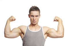 Muscular young man flexing arm muscles in sports outfit. Smiling on white background stock image