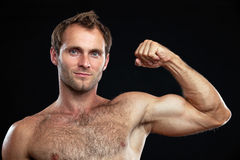 Muscular young man flexing his bicep Stock Photos