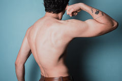 Muscular young man flexing his bicep Royalty Free Stock Image