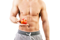 Muscular young man holding an apple Stock Images
