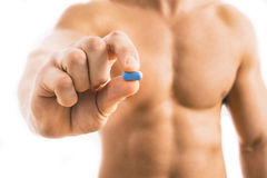 Muscular young man holding blue pill Stock Photography