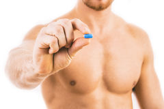 Muscular young man holding blue pill Royalty Free Stock Photos
