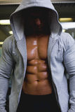 Muscular young man in hood jacket. At the gym Royalty Free Stock Photography