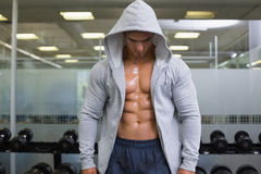 Muscular young man in hood jacket. Standing at the gym Royalty Free Stock Photo