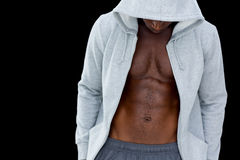 Muscular young man in hood jacket. Standing over black background Stock Photo