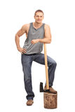 Muscular young man leaning over an axe Stock Photography