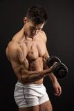 Muscular young man lifting a dumbbell Stock Photography