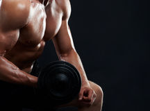 Muscular young man lifting weights on black background royalty free stock photos