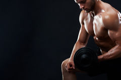Muscular young man lifting weights on black background stock images