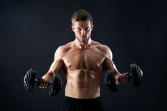 Muscular young man lifting weights on black background. Handsome young fierce muscular male athlete with stunning sexy body and perfect abs looking confidently Royalty Free Stock Image