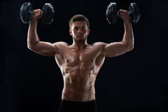 Muscular young man lifting weights on black background stock image