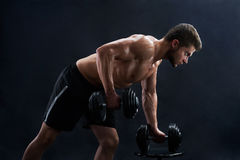 Muscular young man lifting weights on black background stock photos
