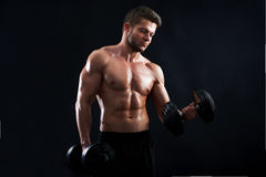 Muscular young man lifting weights on black background. Horizontal studio shot of a young sexy male athlete exercising with heavy weights on black background Royalty Free Stock Photos
