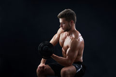 Muscular young man lifting weights on black background stock photo