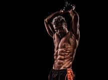 Muscular young man lifting weights on dark background Stock Photos