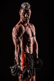 Muscular young man lifting weights on dark background Royalty Free Stock Photos