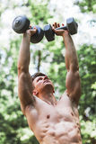 Muscular young man lifting weights. Outside in the park royalty free stock photos