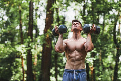 Muscular young man lifting weights in the park. Muscular young man lifting weights outside in the park stock image