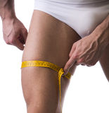 Muscular young man measuring thigh with tape measure Stock Images