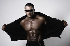 Muscular young man opening his jacket Stock Photography