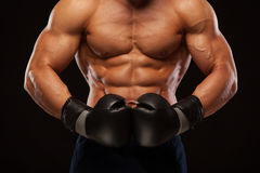 Muscular young man with perfect Torso with six pack abs, in boxing gloves is showing the different movements and strikes. Isolated on black background with Stock Photo