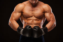 Muscular young man with perfect Torso with six pack abs, in boxing gloves is showing the different movements and strikes. Isolated on black background with Royalty Free Stock Photo