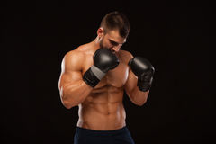 Muscular young man with perfect Torso with six pack abs, in boxing gloves is showing the different movements and strikes. Isolated on black background with Royalty Free Stock Images