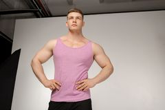 Muscular young man in pink t-shirt posing with hands on belt stock photography