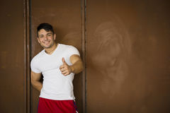 Muscular young man portrait indoors smiling, doing thumb up sign Royalty Free Stock Photo