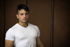Muscular young man portrait indoors, wearing white t-shirt Stock Images