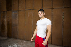 Muscular young man portrait indoors, wearing white t-shirt Stock Photography