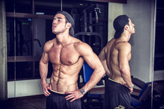 Muscular young man resting in gym during workout Royalty Free Stock Images
