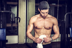 Muscular young man resting in gym during workout Royalty Free Stock Photo